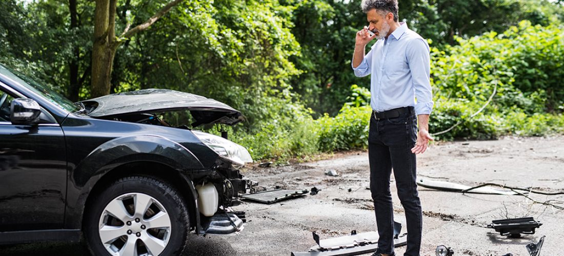 Mature handsome man standing by the car, making a phone call after a car accident.